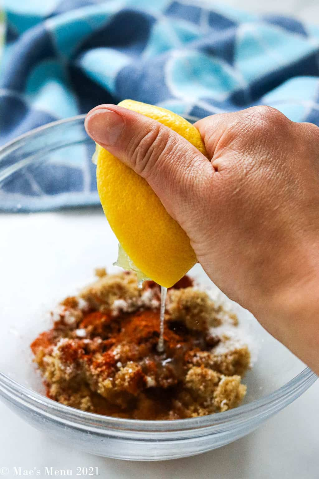 Squeezing lemon over the small bowl of brown sugar and spices