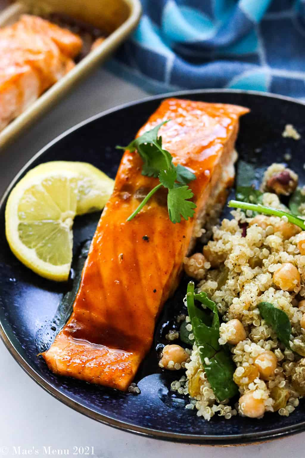 A fillet of bourbon salmon on a blue plate with quinoa salad
