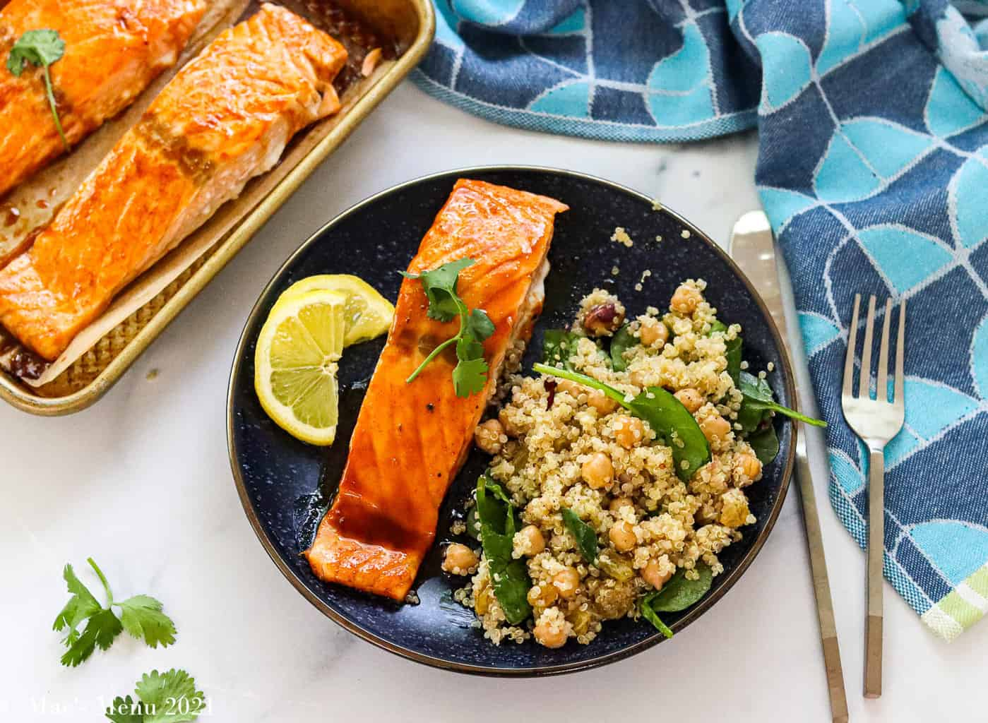 An overhead shot of a plate of bourbon salmon and a serving of quinoa salad with a tray of salmon in th ebackground