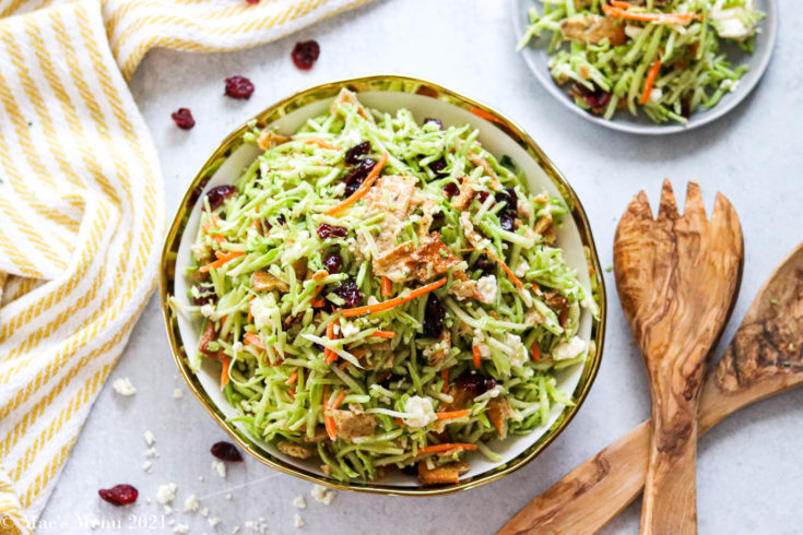A large bowl of broccoli slaw next to salad tongs and a small plate of the slaw