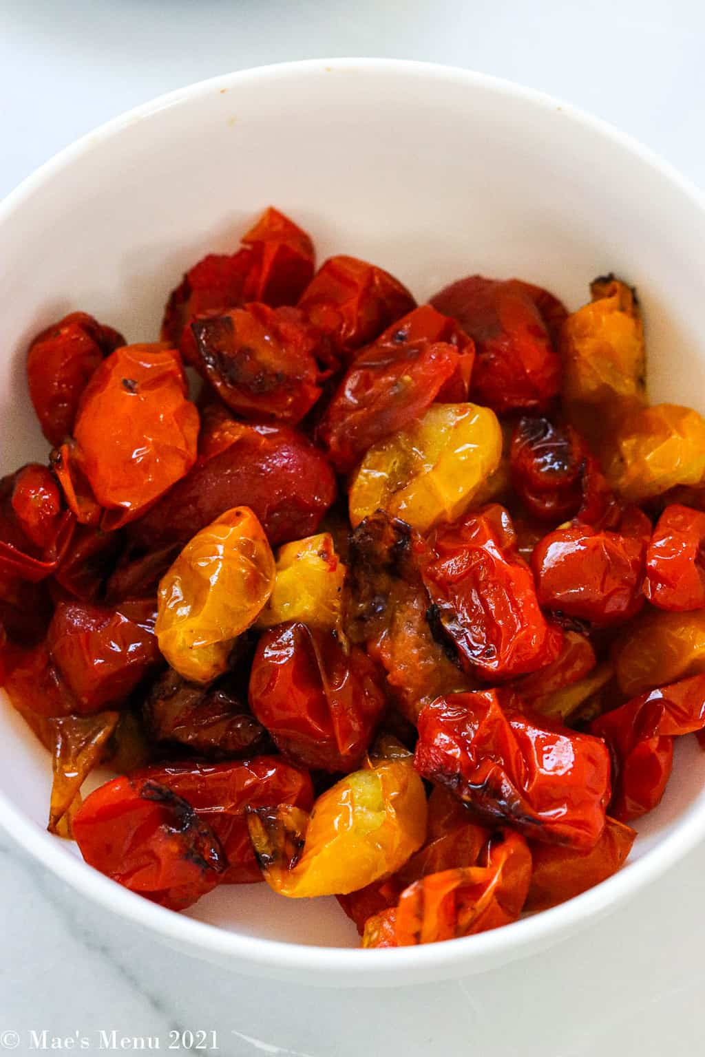 An up close shot of a bowl of roast cherry tomatoes