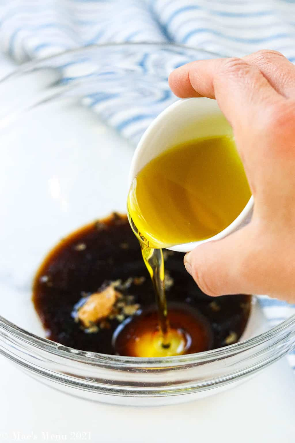Pouring olive oil into a mixing bowl of the balsamic dressing