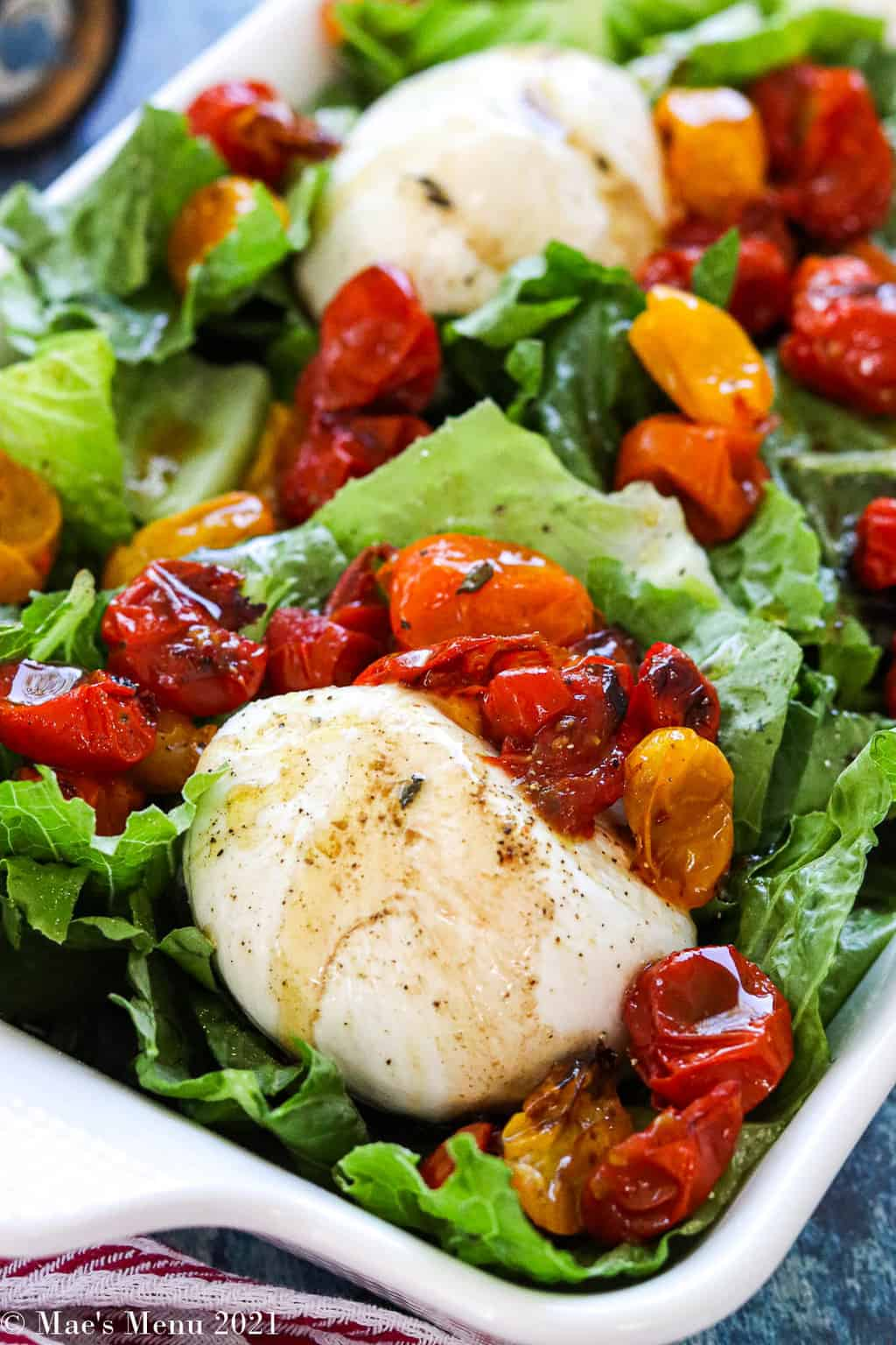 An up-close shot of burrata salad with tomatoes in a white serving platter