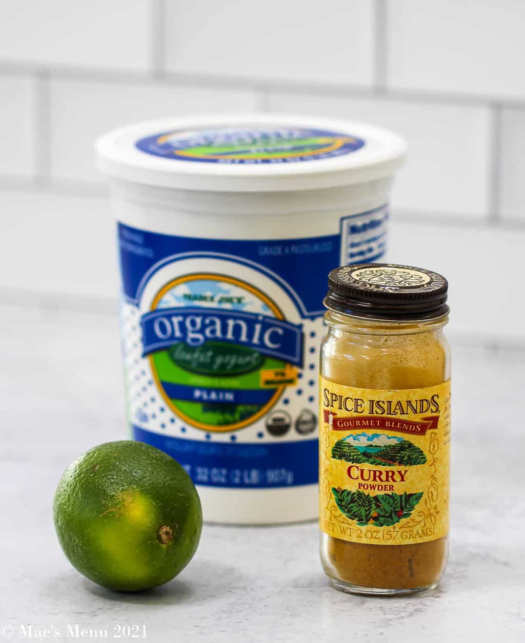 A jar of yogurt, lime, and bottle of curry powder