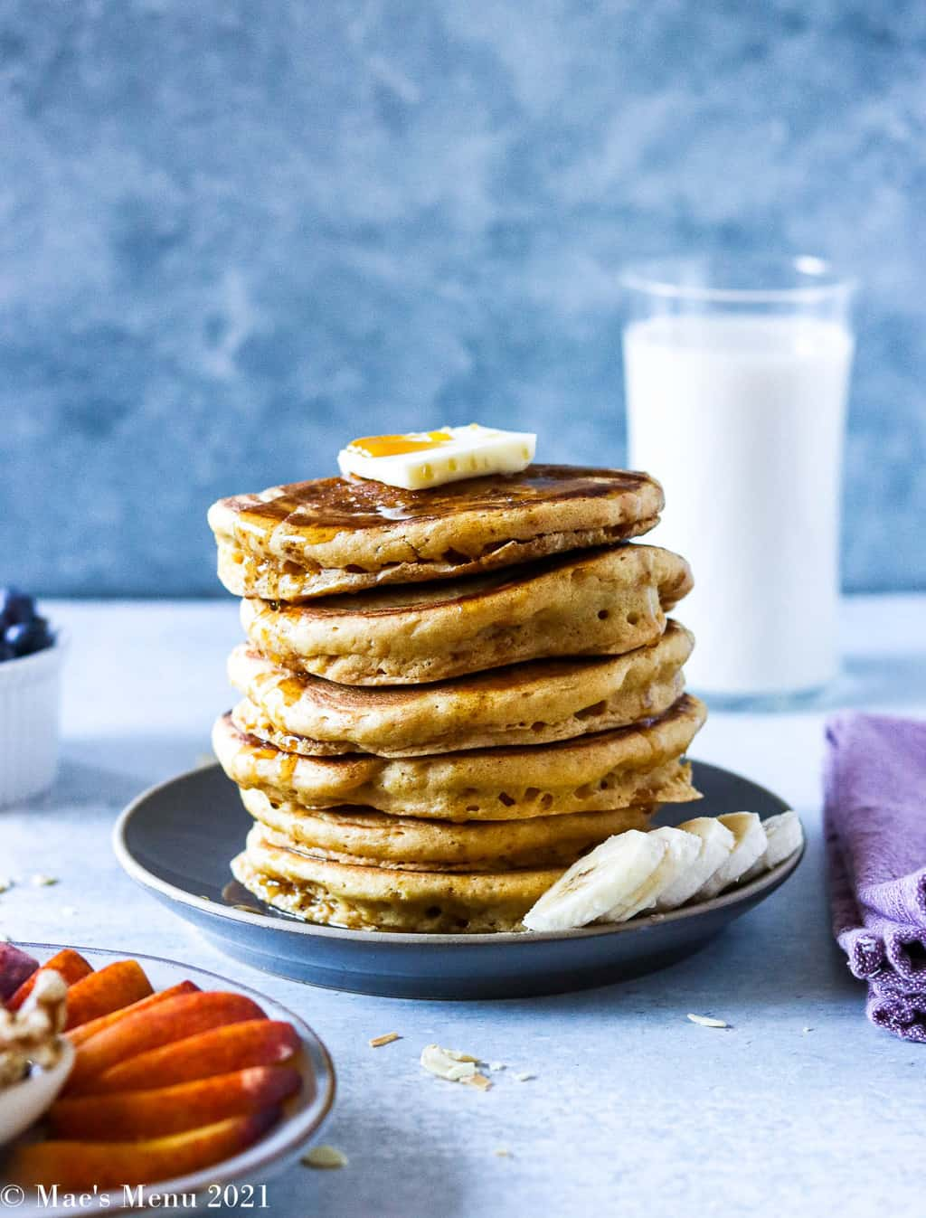 A large stack of whole wheat pancakes on a plate surrounded by fruit and a glass of milk