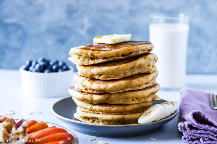 A stack of fluffy whole wheat pancakes on a grey plate with blueberries and milk in the background