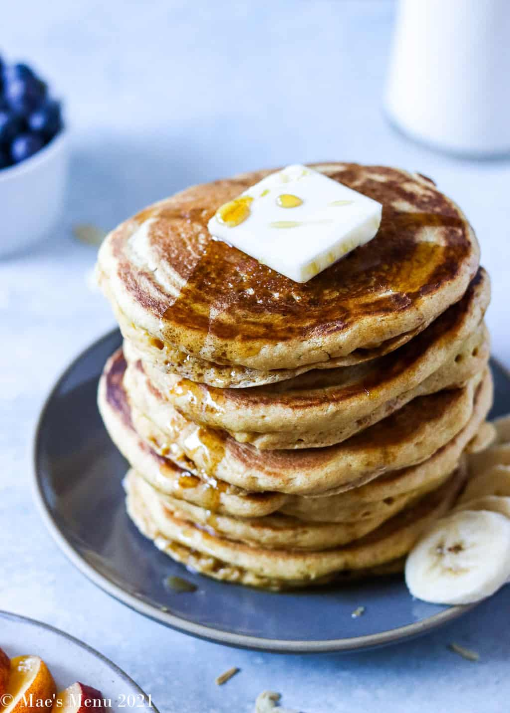 An elevated side shot of a stack of pancakes with butter on top