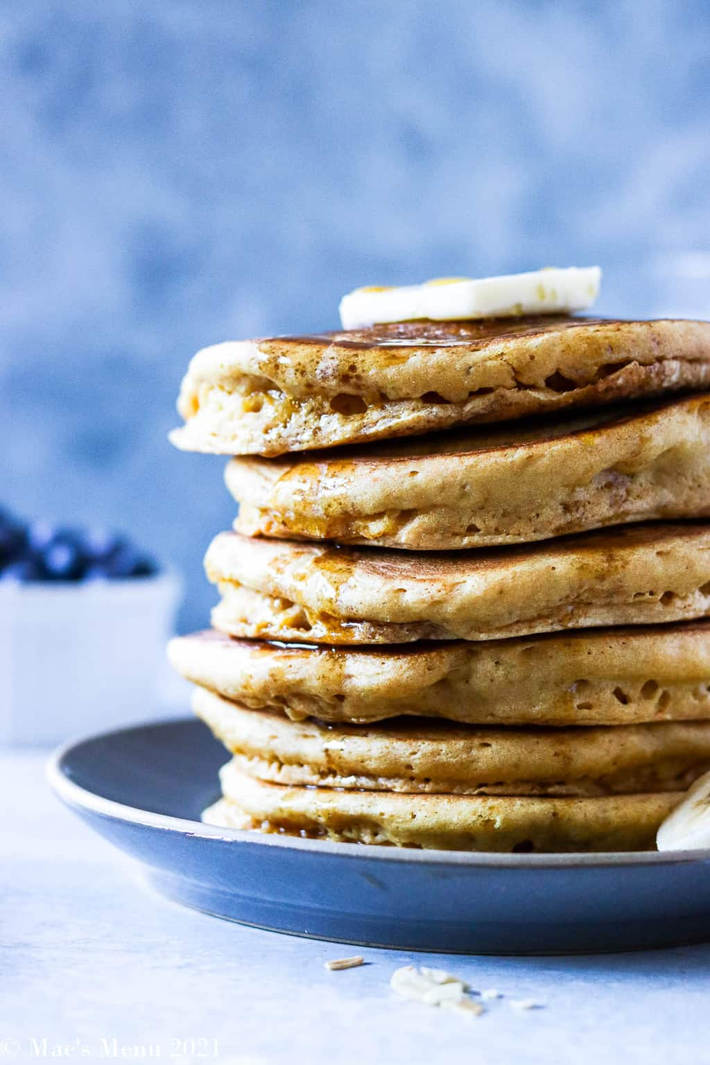 An up-close side shot of a stack of pancakes with butter and syrup dripping down the side