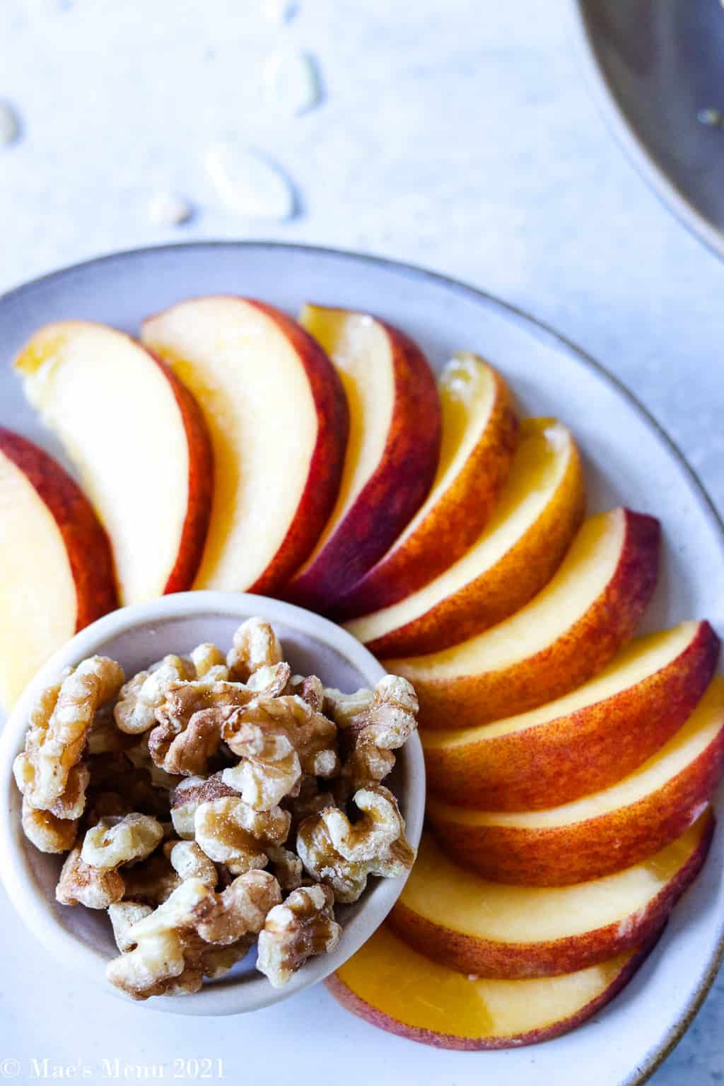 An overhead shot of a sliced peach and walnuts
