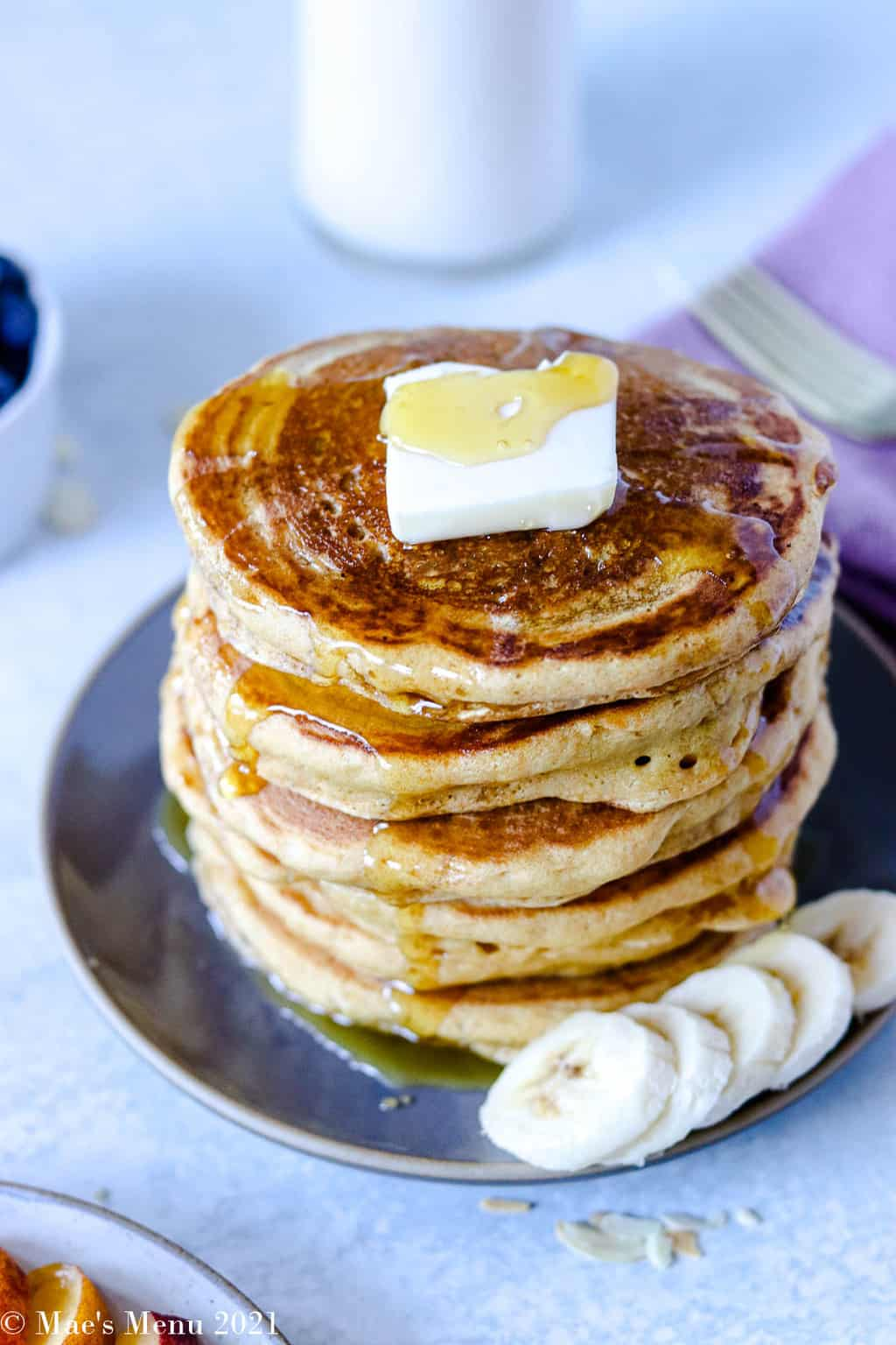 An elevated shot of a stack of pancakes with butter and bananas