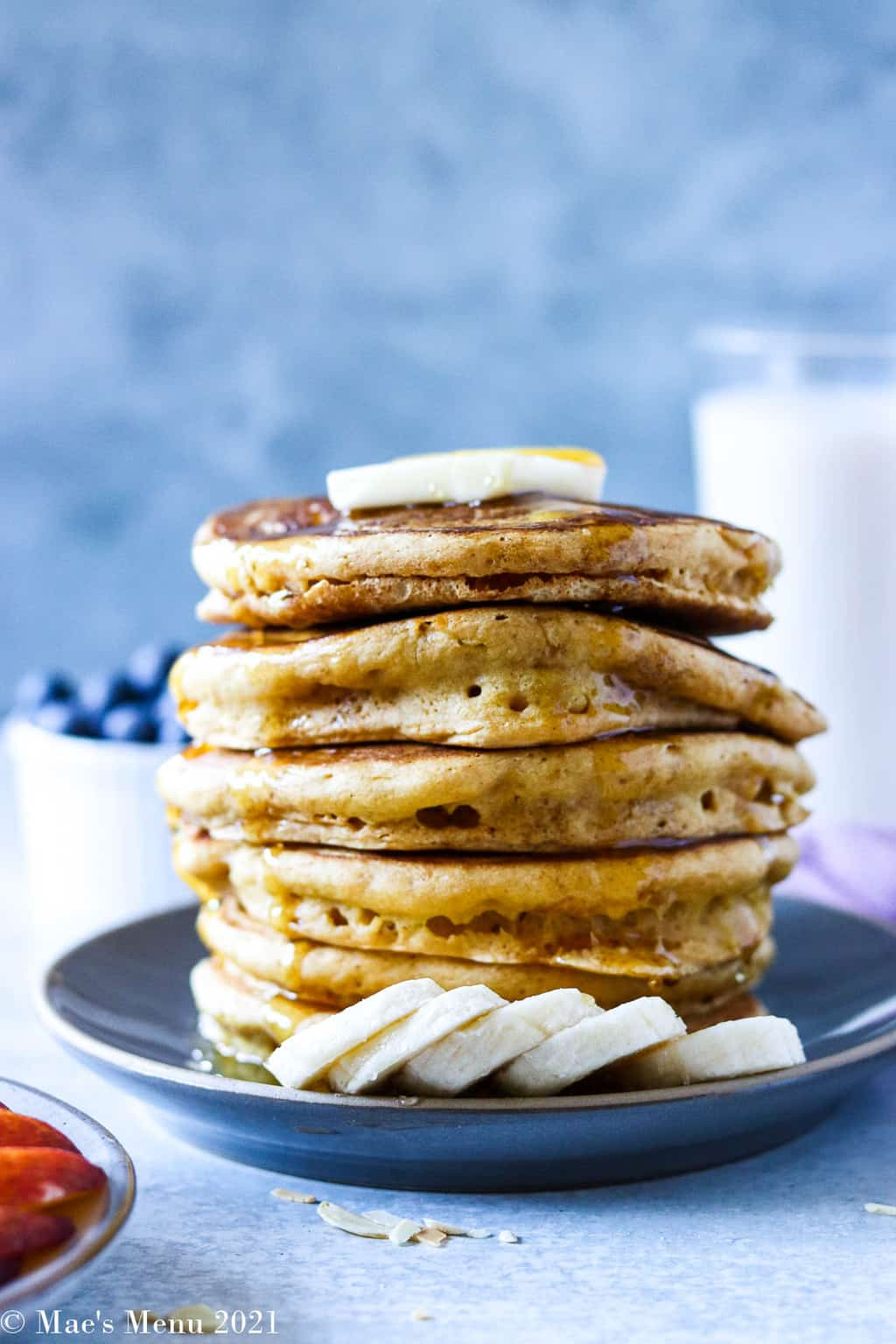 An up-close side shot of a large stack of pancakes with bananas and butter