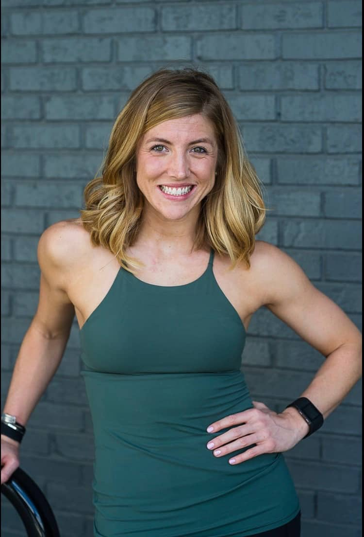 Katie Hake,  a dietitian, standing in front of a grey brick wall.