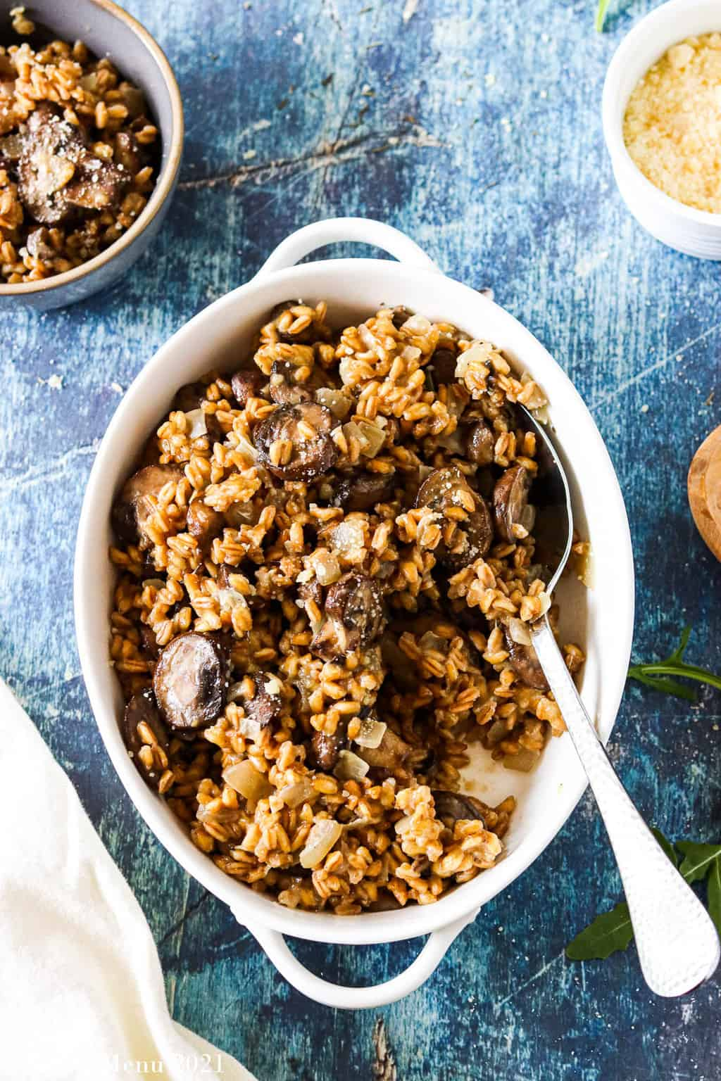 An overhead shot of a bowl of mushroom farro risotto with a spoon in it. The bowl is surrounded by a cup of cheese and a small dish of risotto