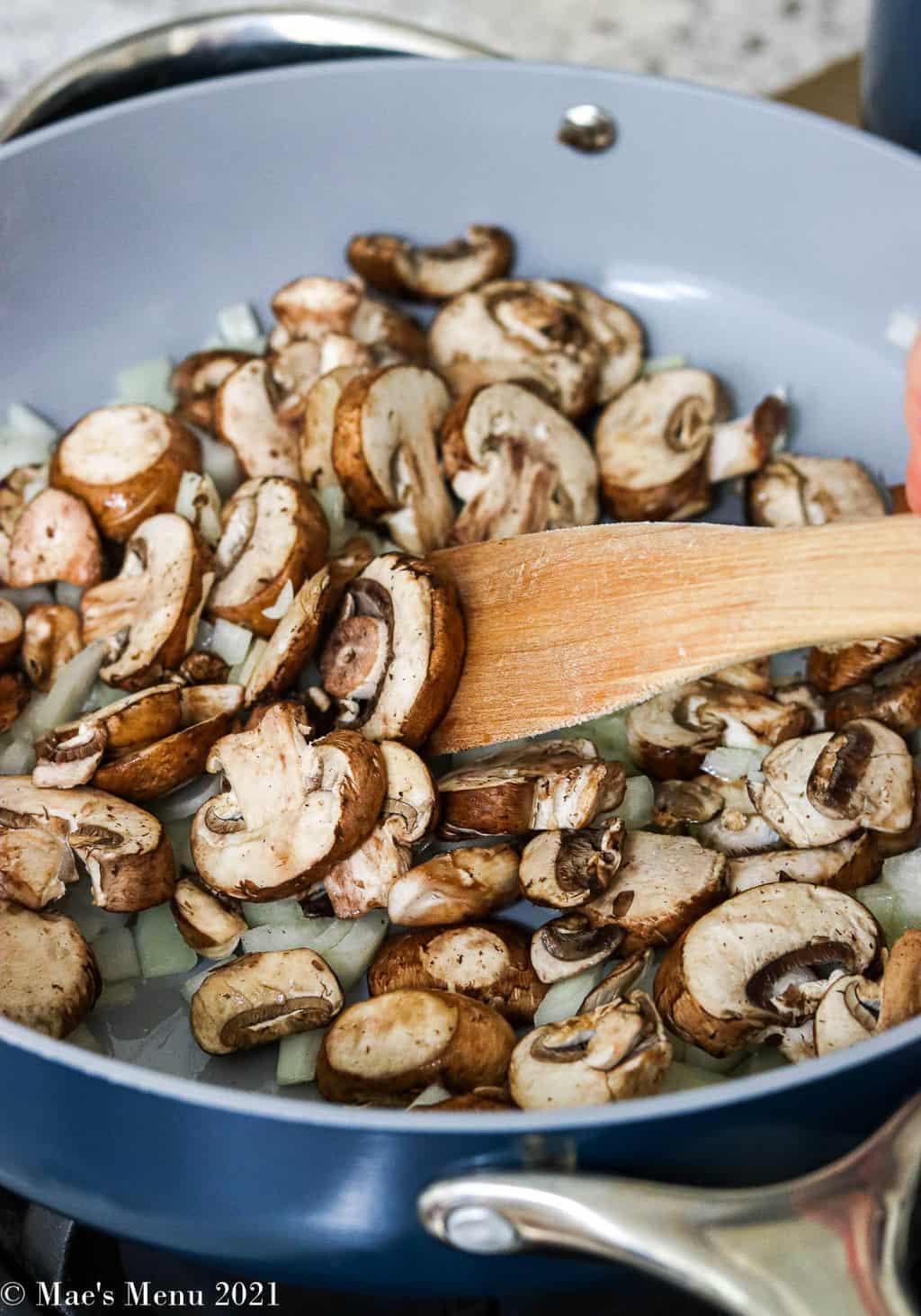 Sauteing mushrooms and onions in oil in a large saute pan