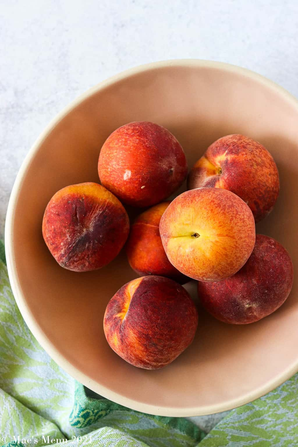 A light peach colored bowl of peaches with a blue towel in he background