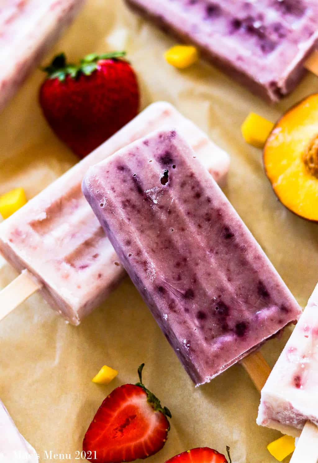 Two popsicles laying on a sheet of parchment paper surrounded by fruit