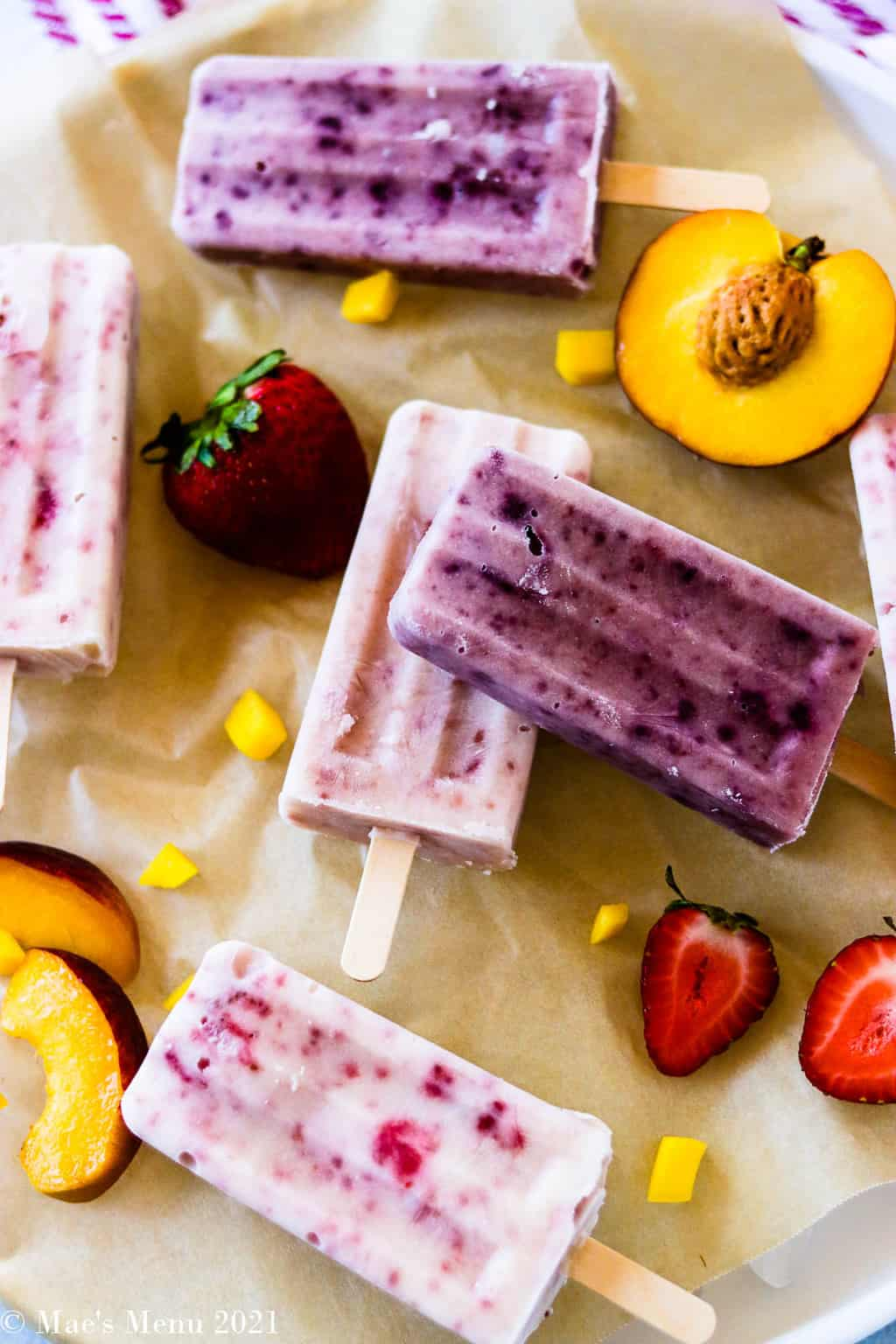 A bunch of fruit and yogurt popsicles laying on a piece of parchment paper