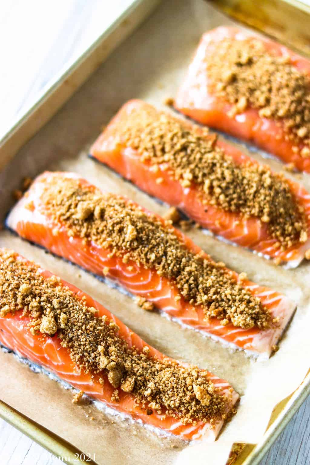 A baking sheet with salmon an a brown sugar spice blend on top of the pieces