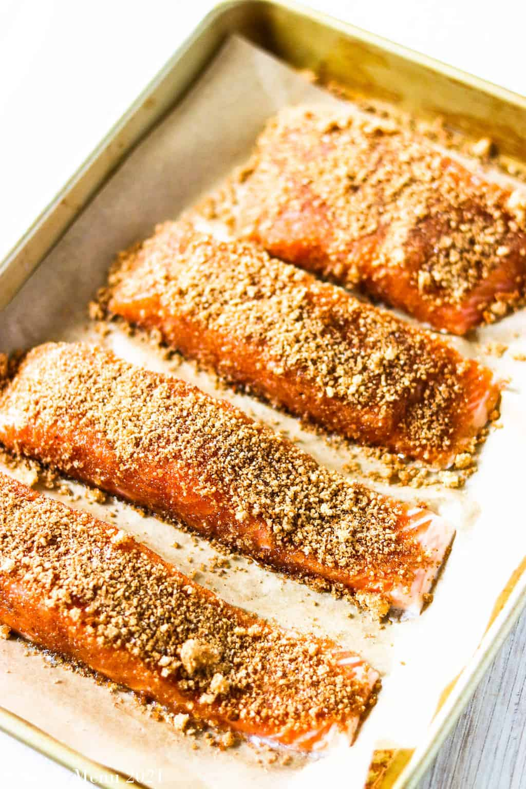 Pieces of salmon on a cuting board with the brown sugar spice blend rubbed on top