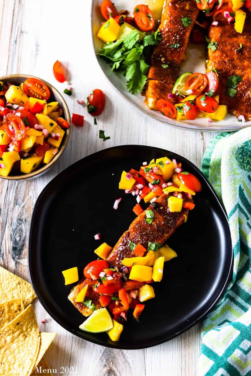 An up close overhead shto of a plate with spicy brown sugar salmon with mango salsa on top