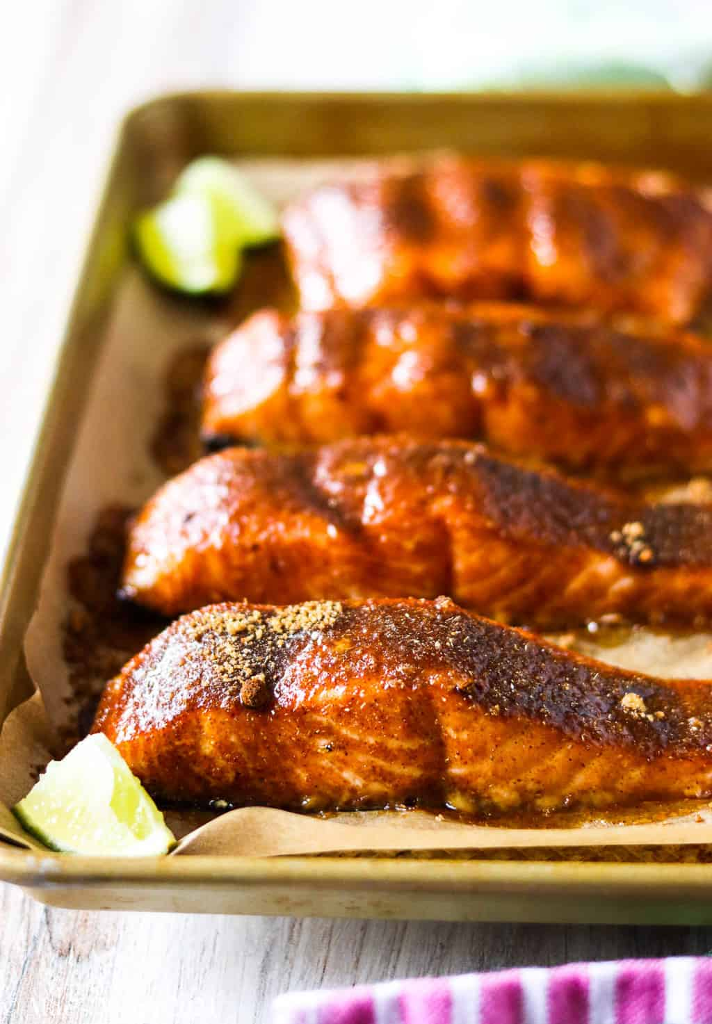 An up close side shot of a pan of spicy brown sugar salmon wih limes