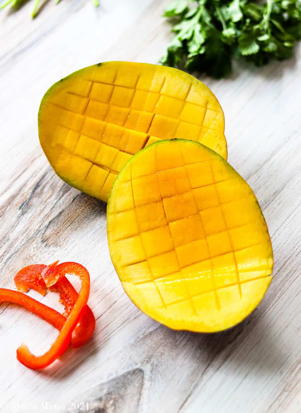 two halves of mango with a crisscross pattern cut ito them