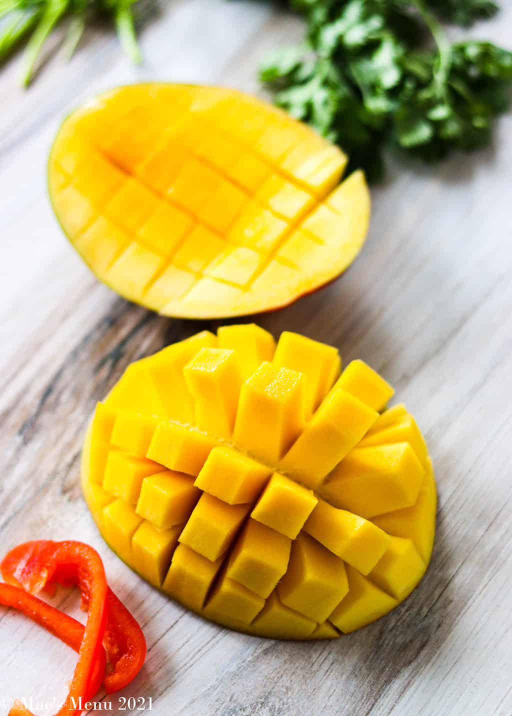 Halves of a mango with the crisscross pattern cut into them. One is popped inside out