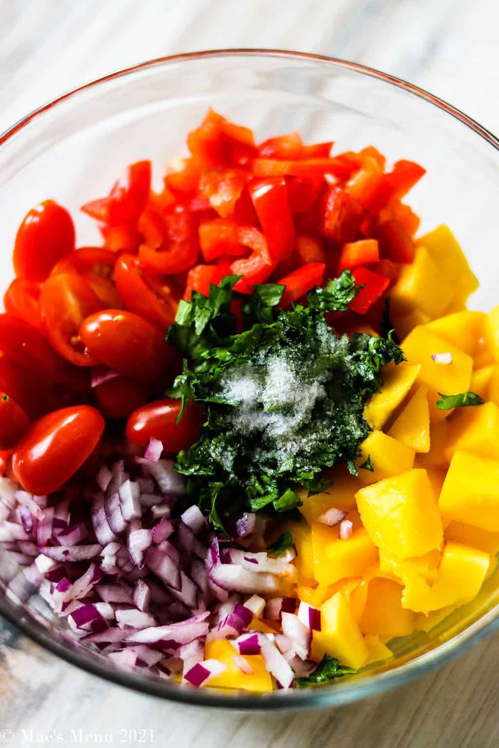 A mixing bowl with diced mango, tomatoes, red onio, red pepper, cilantro, and salt