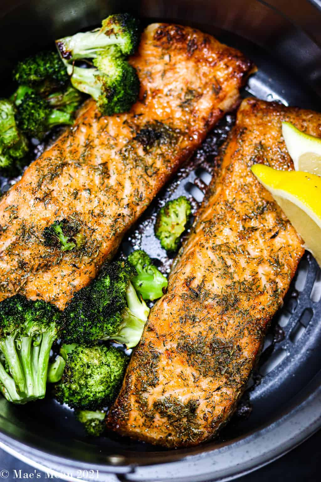 Two cooked pieces of air fryer salmon in a basket with broccoli and lemon