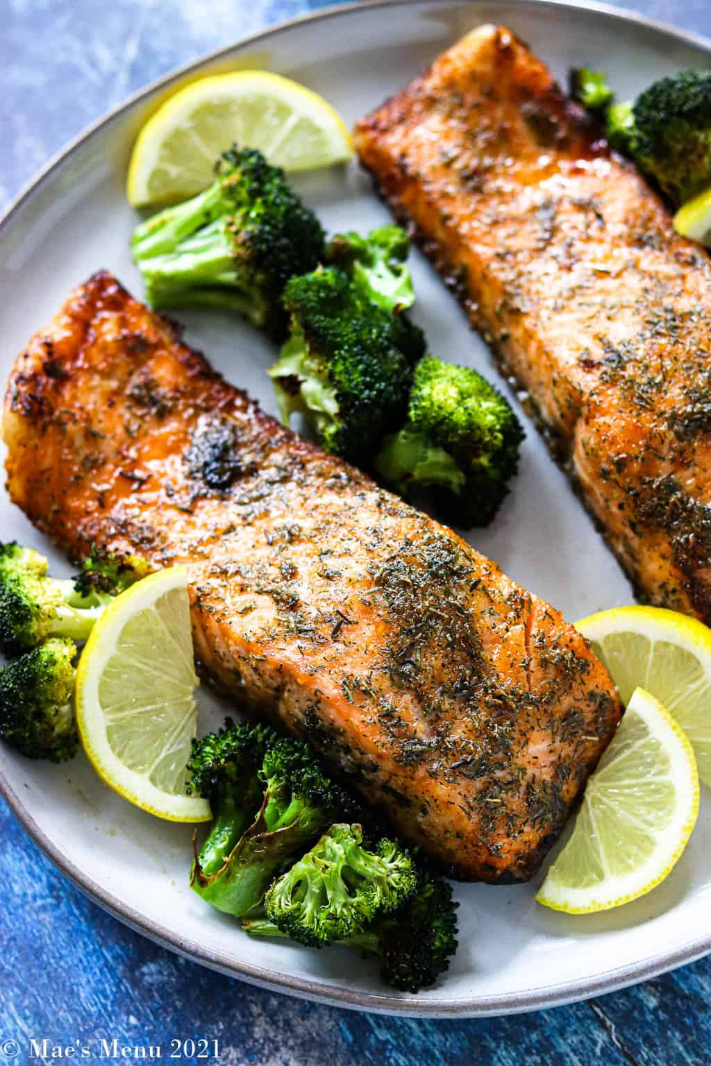 Two large pieces of air fryer salmon on a serving plater with broccoli and lemons