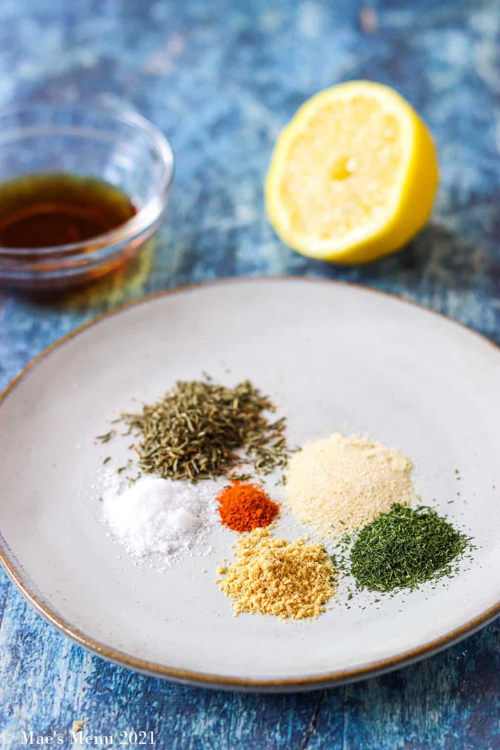 An up-close shot of spices on a plate with lemons and a dish of maple syrup in the background