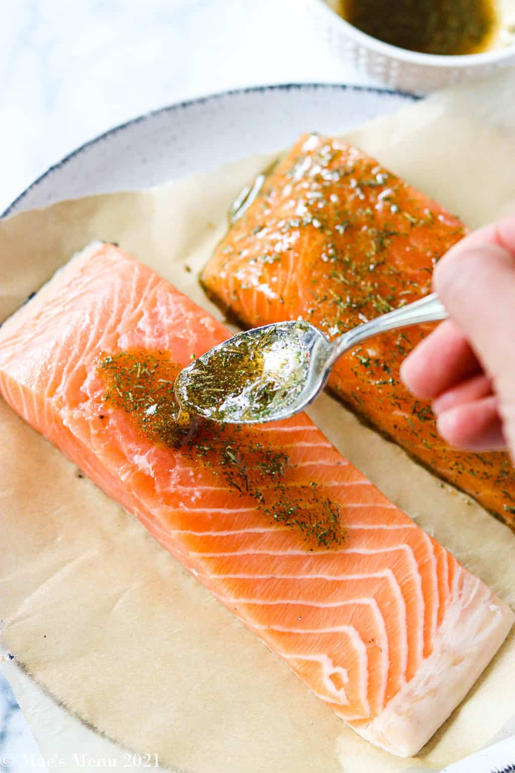 Drizzling the herb & maple glaze over the pieces of salmon