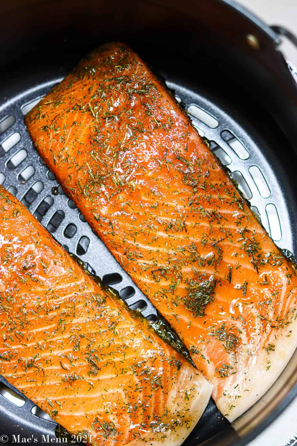 Two large spices of salmon brushed with glaze in an air fryer basket