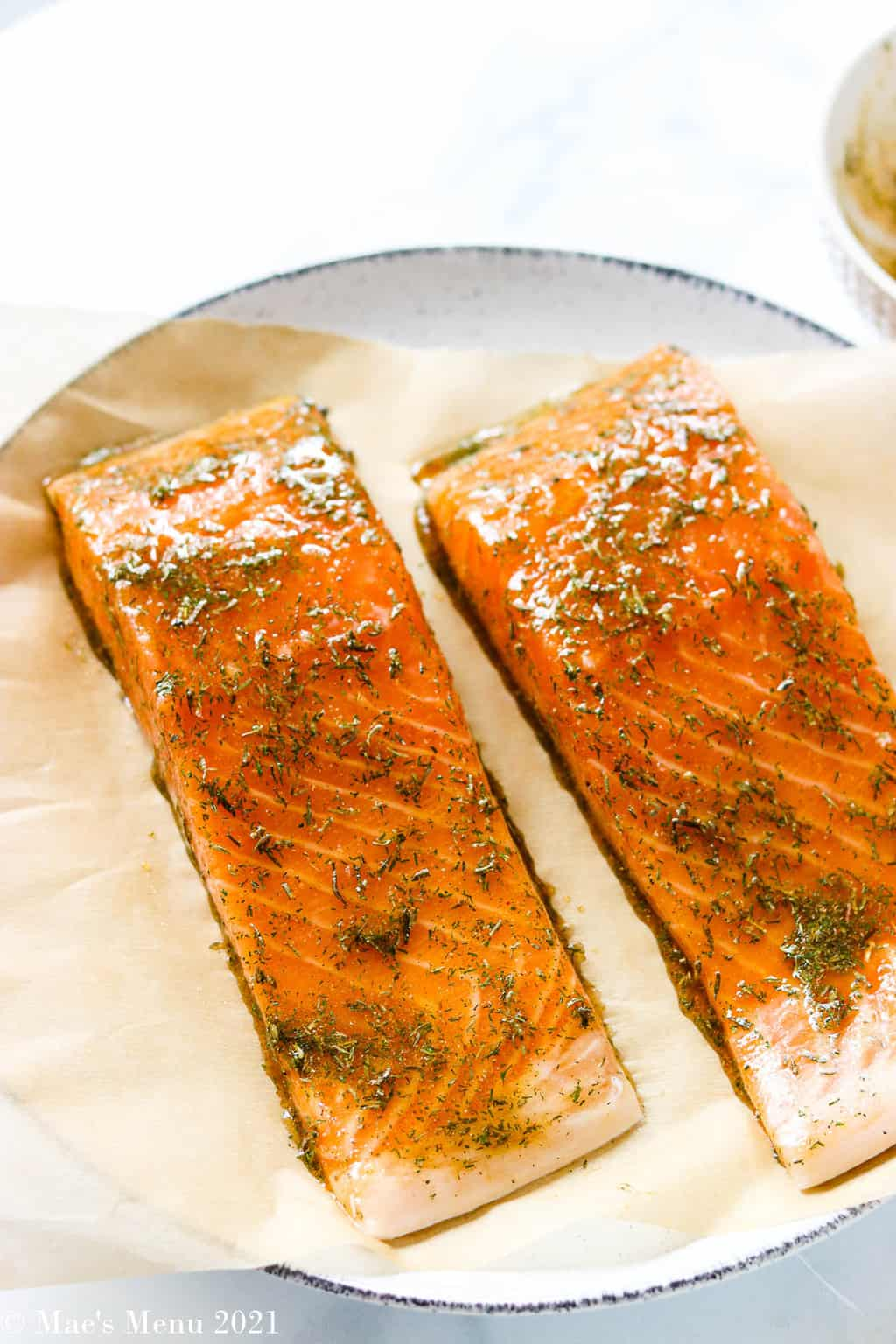Two large pieces of salmon brushed with the glaze on a plate
