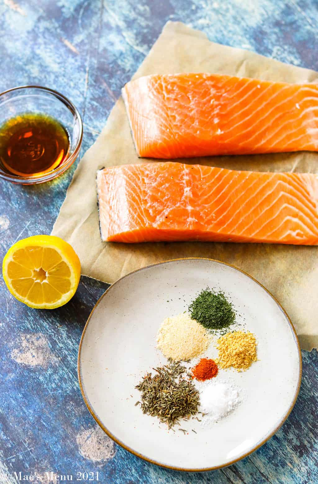 All the ingredents for air fryer salmon: salmon, spices, lemon, and maple syrup