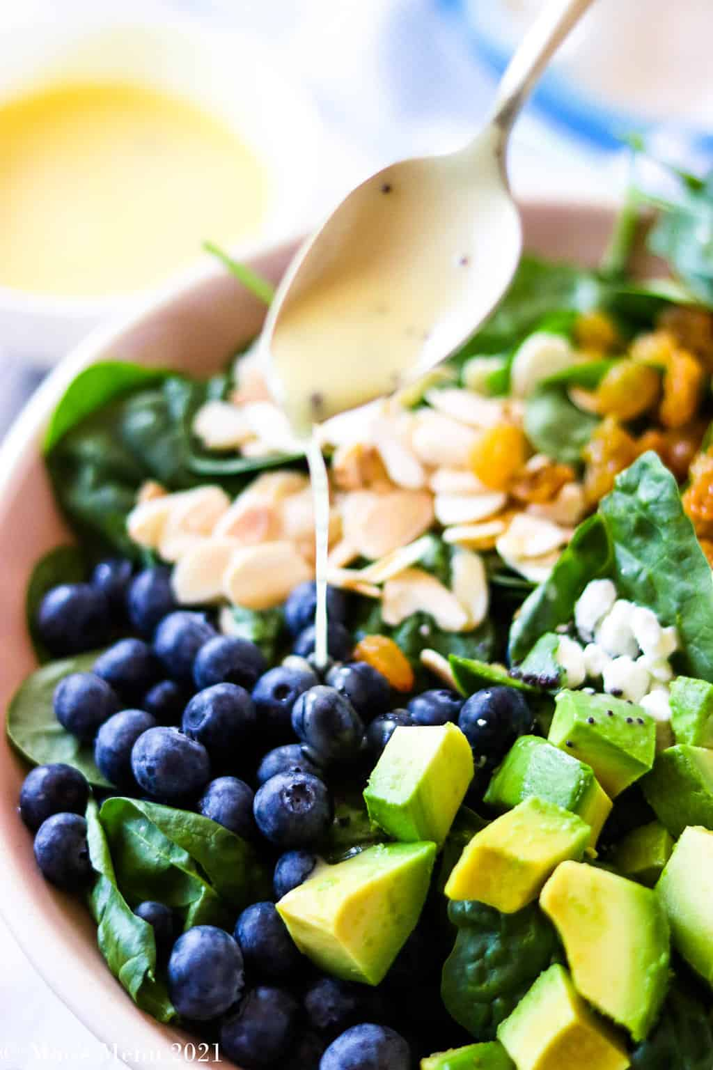 Dressing the blueberry spinach salad with the homemade poppy seed dressing recipe