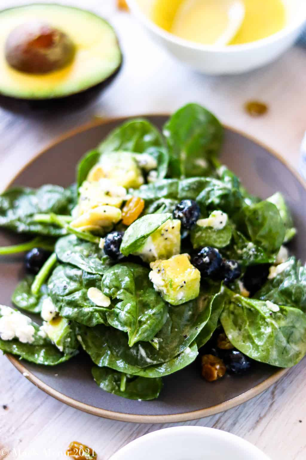 A side shot of a small dish of avocado blueberry spinach salad