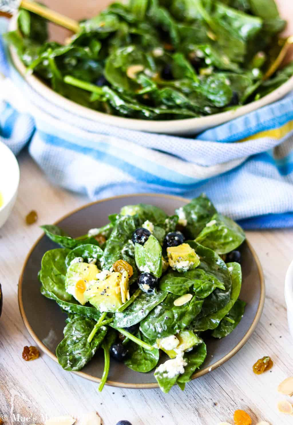 A small plate of blueberry spinach salad in front of the bowl of salad