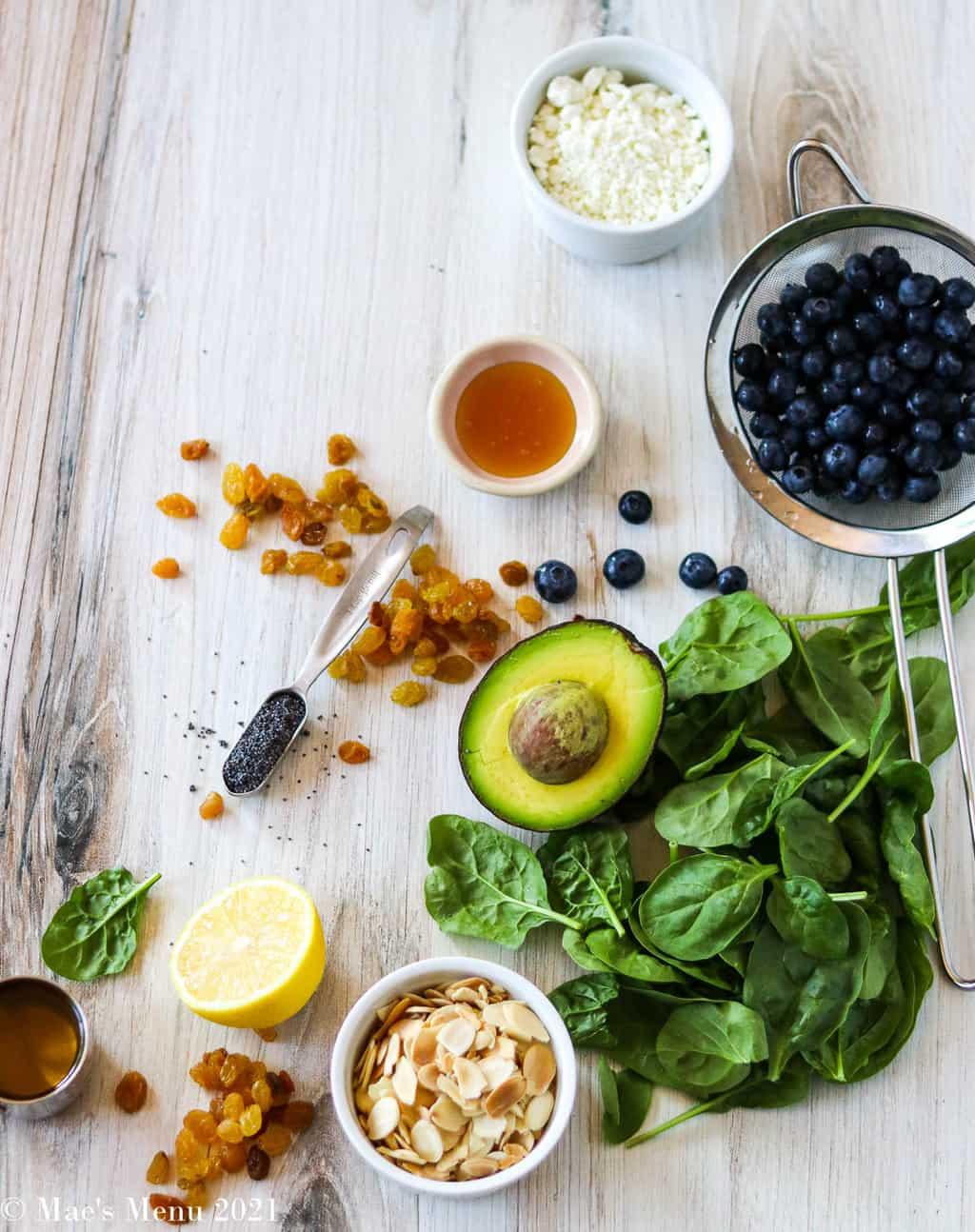 All of the ingredients for this recipe: goat cheese, blueberries, avocado, spinach, golden raisins, honey, almonds, poppy seeds, lemon, and olive oil