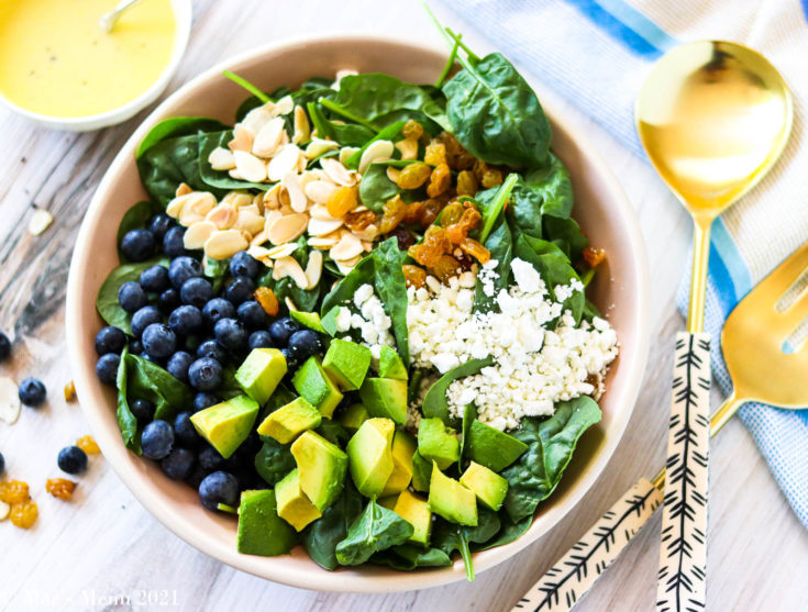 A horizontal shot of a large bowl of blueberry avocado salad surrounded by a dish of dressing and salad tongs