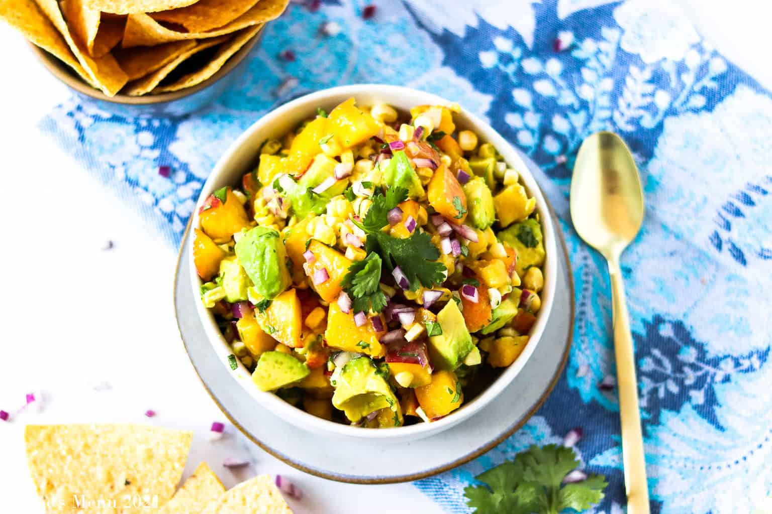 A horizontal shot of a bowl of avocado peach salsa surrounded by a spoon and tortilla chips
