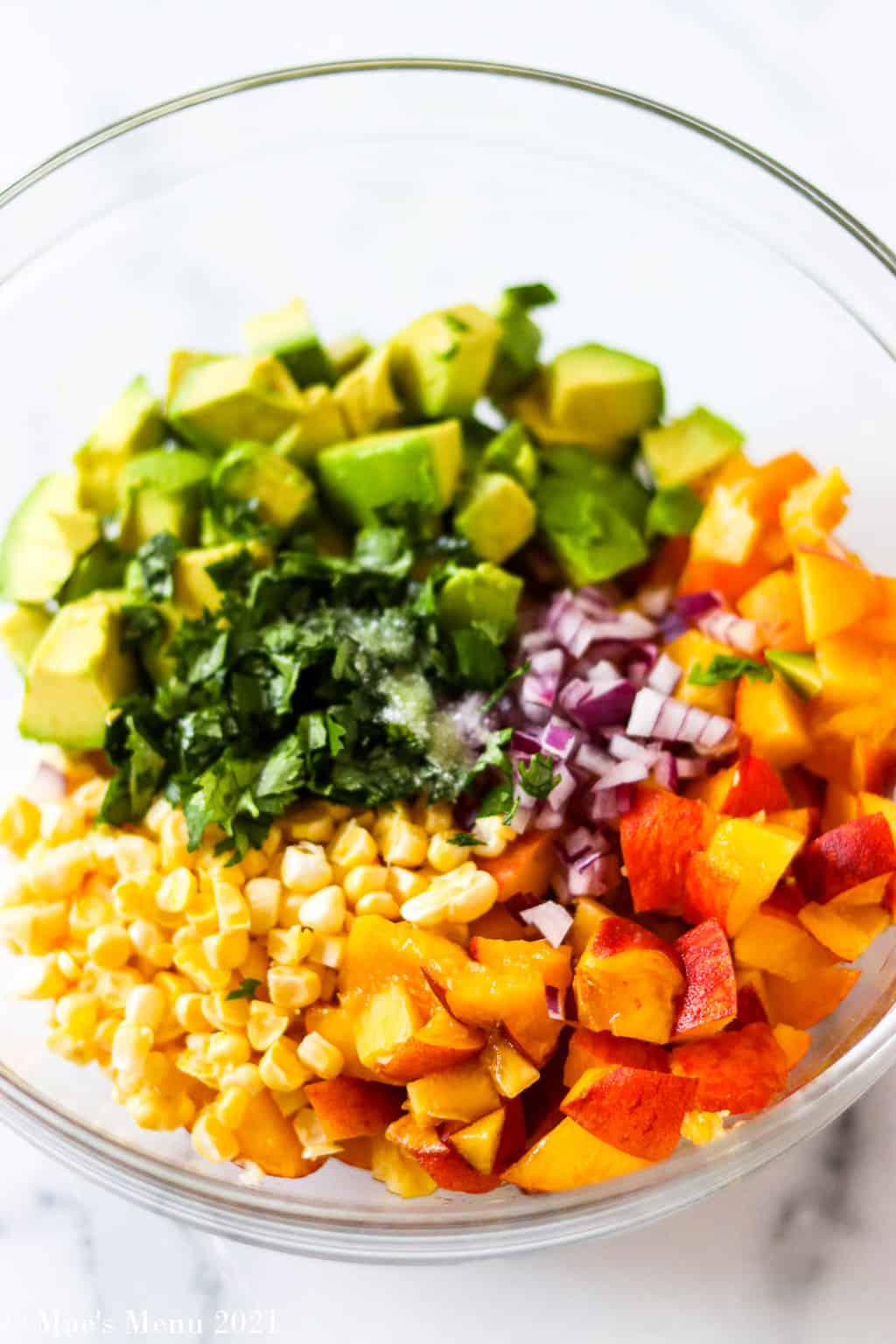 an overhead shot of a mixing bowl full of avocado peach salsa ingredients