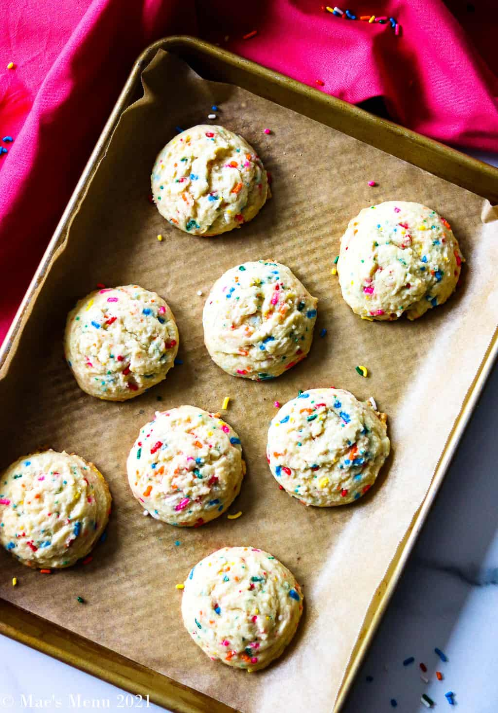 A small baking sheet of funfetti sugar cookies with a pink towel in the background