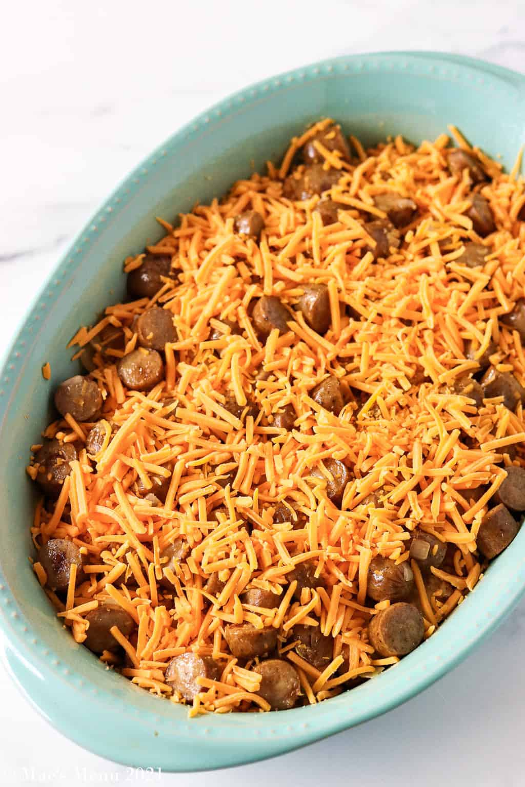 A blue baking pan with chicken sausage and shredded cheese