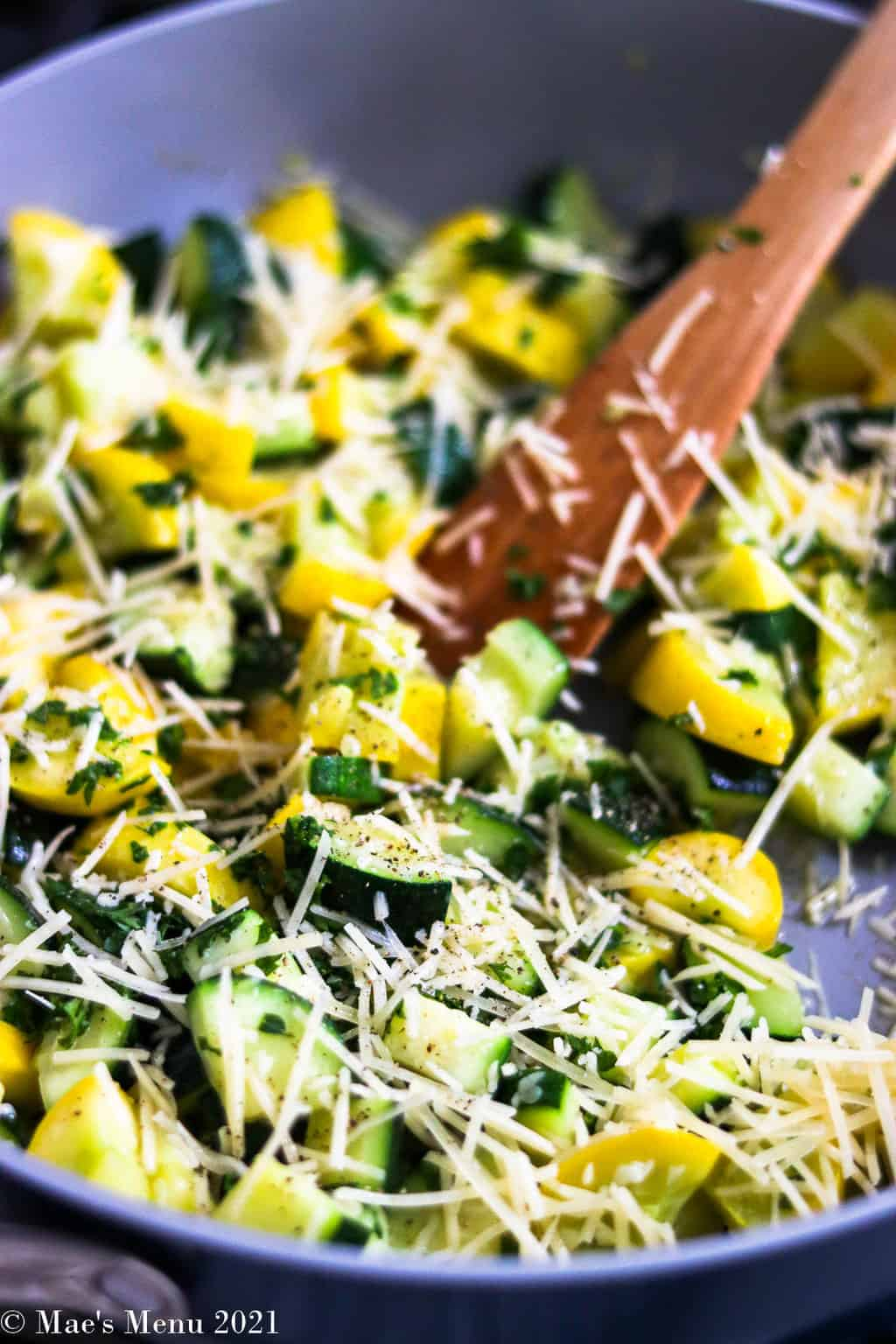 A side angle shot of a pan of sauteed yellow squash and zucchini with parmesan cheese and parsley