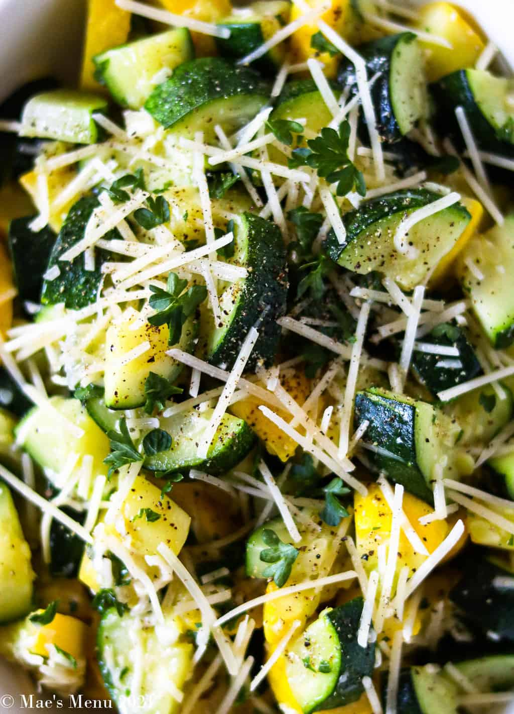 An up-close shot of sauteed zucchini and yellow squash with shredded parmesan cheese and herbs