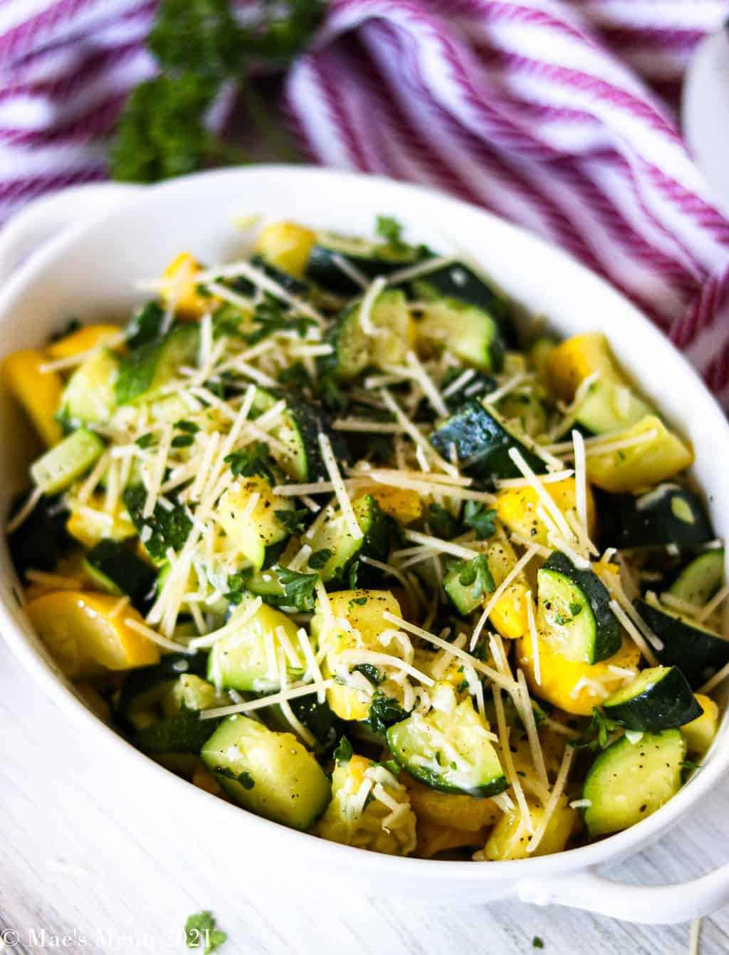 A side angle shot of zucchini and yellow squash in a white serving bowl