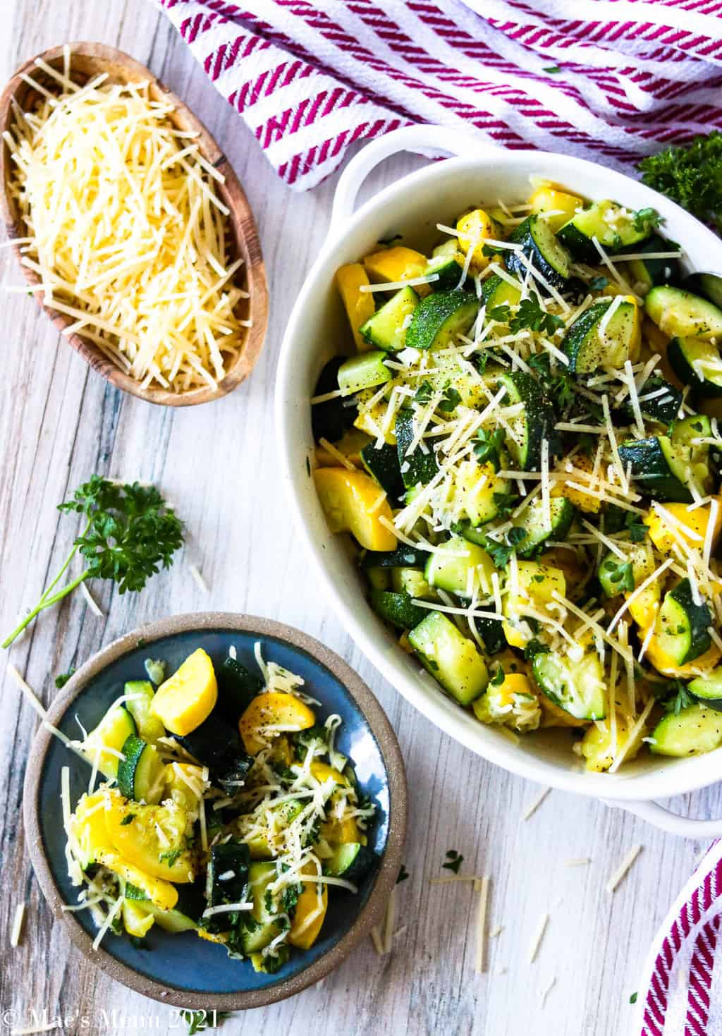 A small dish of sauteed zucchini and yellow squash next to a white serving bowl of it