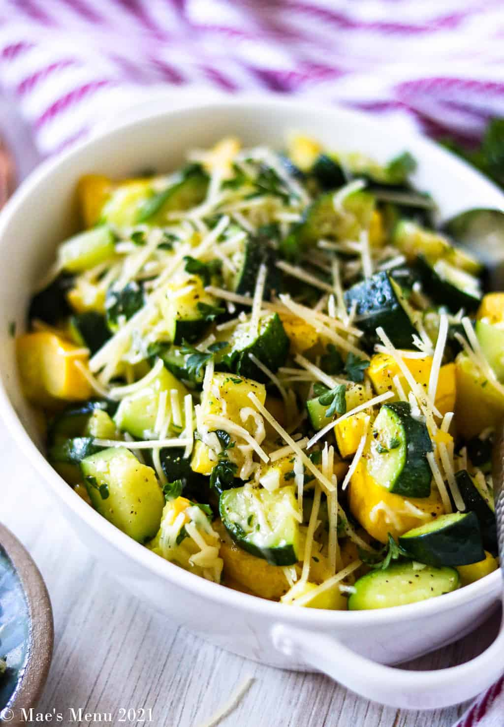 An up-close side shot of a bowl of sauteed zucchini and yellow squash
