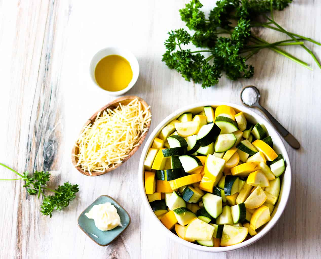 All the ingredients for sauteed zucchini and yellow squash: a bowl of zucchini, grated parmesan cheese, butter, salt, and parsley